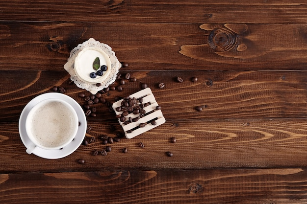 Koffiebonen verspreid over een houten standaard en een kopje koffie met bosbessencake