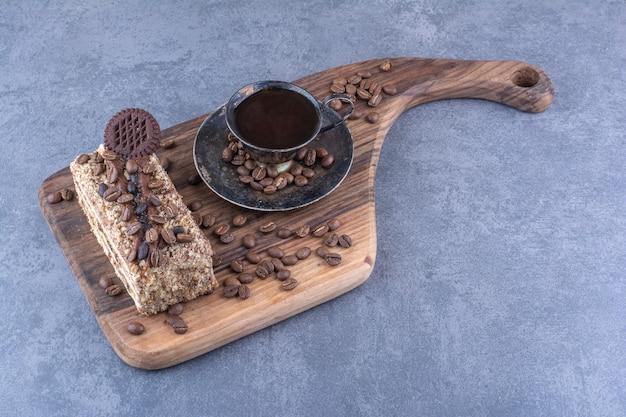 Koffiebonen verspreid over een kopje koffie en een plakje cake op een houten bord op een marmeren oppervlak