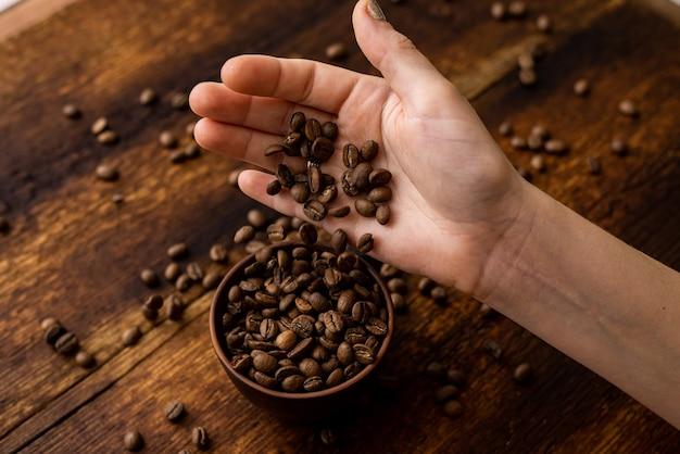 Koffiebonen volle kop en vrouwelijke handen op bruine oude houten achtergrond.