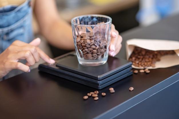 Koffiebonen, wegen. vrouwelijke slanke handen met een gewicht van koffiebonen in glas op kleine schaal op de teller