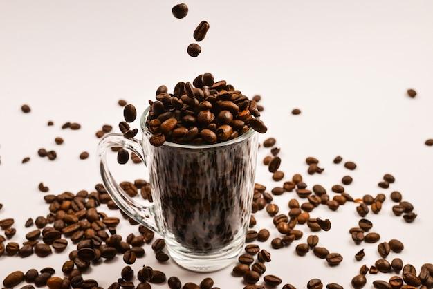 Koffiebonen worden in een glazen beker op een witte achtergrond gegoten