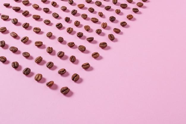 Koffiebonen zijn uitgespreid op een roze achtergrond
