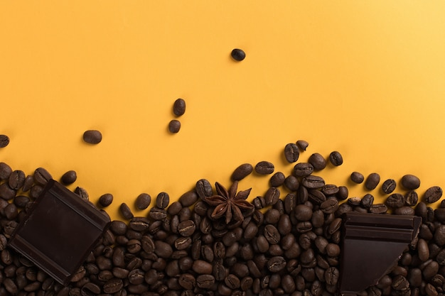 Koffiebonen zijn verspreid op een geel papier en chocolade, commerciële copyspace.