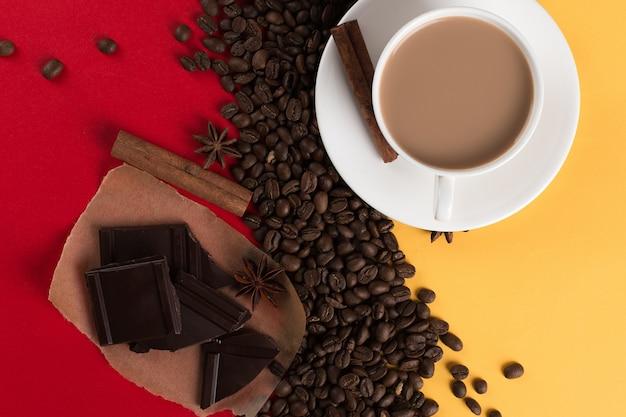 Koffiebonen zijn verspreid op een rood en geel papier en een witte kop, kaneel, steranijs, chocolade, commerciële copyspace.