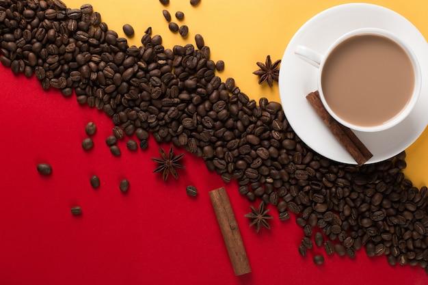 Koffiebonen zijn verspreid op een rood en geel papier en een witte kop, kaneel, steranijs, commerciële copyspace.