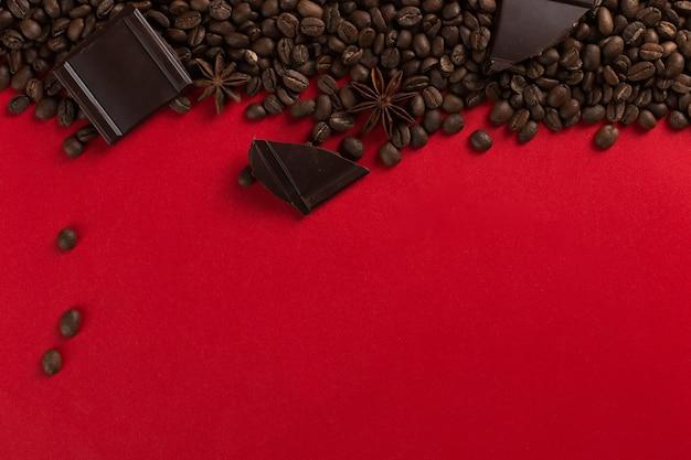 Koffiebonen zijn verspreid op een rood papier en chocolade, commerciële copyspace.
