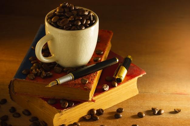 Koffieboon in de witte kop en het uitstekende boek die op houten lijst in ochtendlicht stapelen.