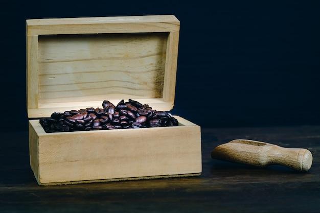 Koffieboon in houten doos op oude houten achtergrond.