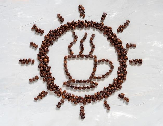Koffieboon in kop en zonvorm op witte vloer