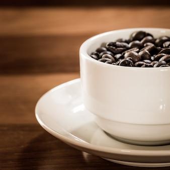 Koffieboon in kop op houten lijst