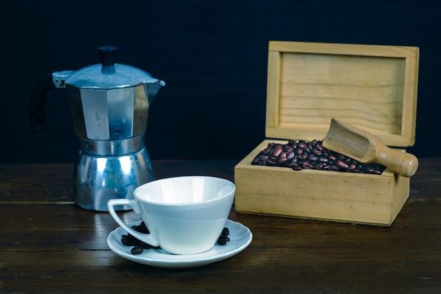 Koffieboon in witte koffiekop op oude houten achtergrond.