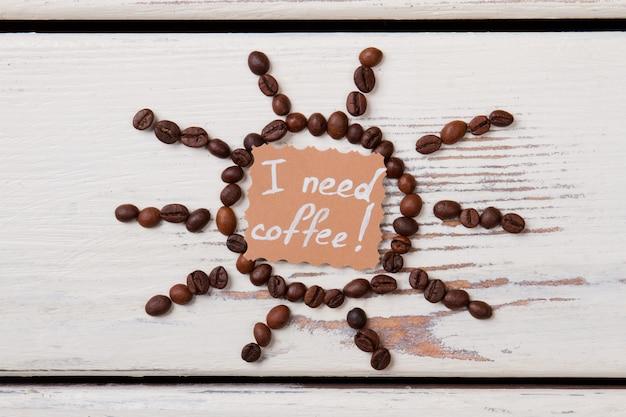 Koffieboonzon en papier met ik heb koffie nodig om te schrijven. wit houten oppervlak.