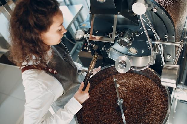 Koffiebrander machine en barista met tryer bij koffiebranderingsproces.