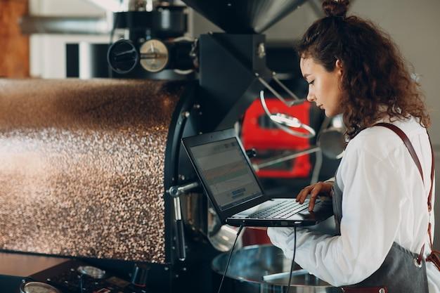 Koffiebrander machine en barista vrouw met laptop bij koffiebranderingsproces