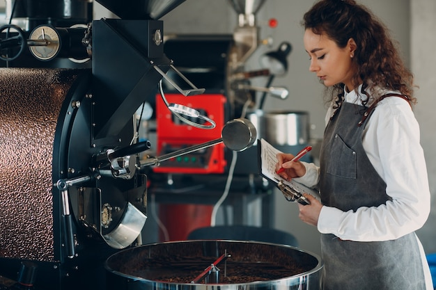 Koffiebrandermachine en baristavrouw met tabletschrijfpen bij koffiebrandproces