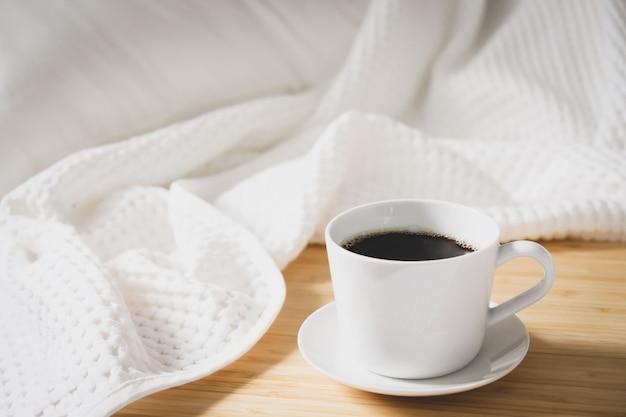 Koffiebrood in een witte kop die op het bed wordt geplaatst