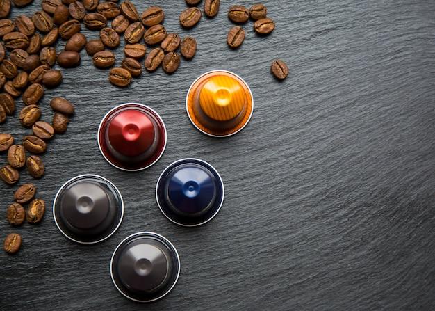 Koffiecapsules en koffiebonen op grijze lijst