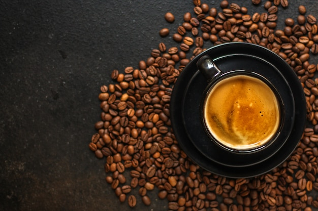 Koffiedrank in witte kop en strooi koffiebonen op de tafel