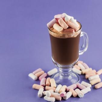 Koffiedrank met marshmallow-snoepjes in glazen beker op paars