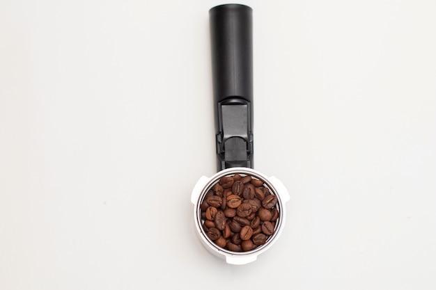 Koffiefilterhouder met koffiebonen op wit bord. bovenaanzicht.