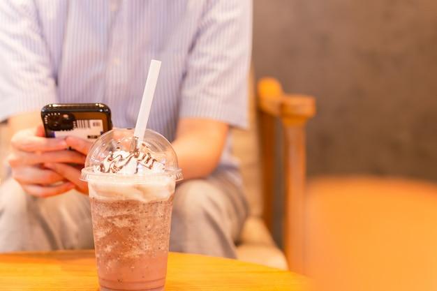Koffiefrappuccino gemengd met papieren rietje en mensen die een mobiele telefoon gebruiken