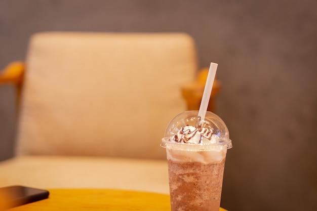 Koffiefrappuccino gemengd met papieren stro op houten tafel.