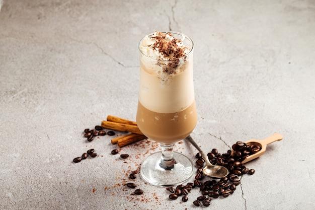 Koffieglace in een glas op het betonnen oppervlak versierd met bonen en kaneel