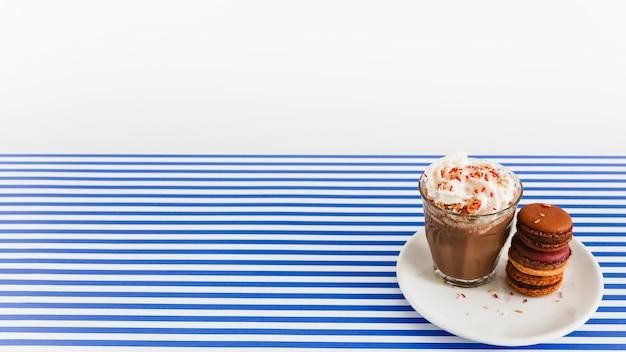 Koffieglas met slagroom en stapel makarons op plaat over achtergrond