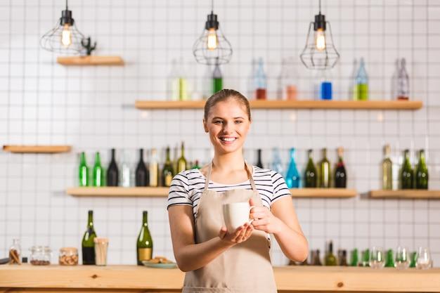 Koffiehuis. vrolijke positieve aardige vrouw die lacht en een kopje met koffie vasthoudt tijdens het werken in de coffeeshop