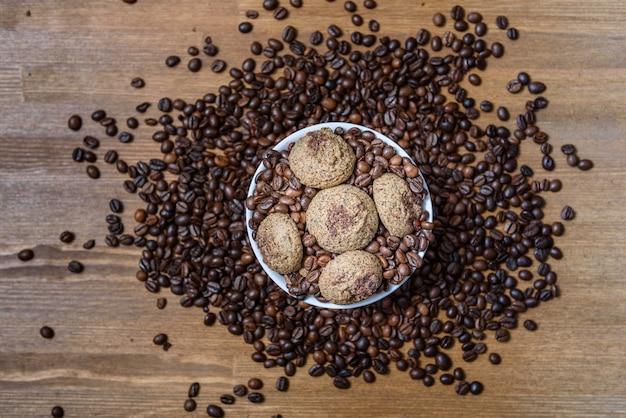 Koffiekoekjes in een witte plaat met koffiebonen op houten bruine tafel