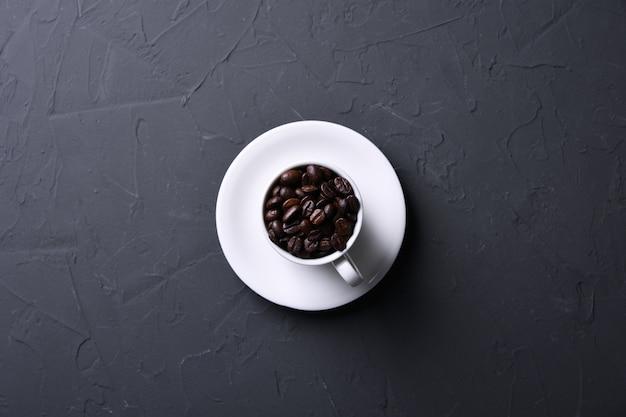 Koffiekop en bonen op oude grijze keuken beton, rotslijst. bovenaanzicht met copyspace voor uw tekst