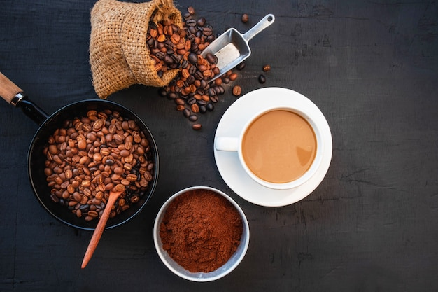 Koffiekop en bonen op zwarte lijst. bovenaanzicht