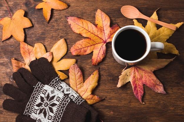 Koffiekop en handschoenen op de achtergrond van de herfstbladeren