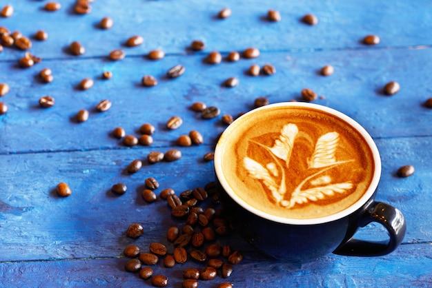 Koffiekop en koffiebonen op blauwe houten achtergrond. bovenaanzicht.