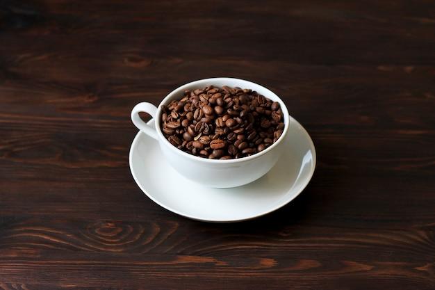 Koffiekop en koffiebonen op houten achtergrond.