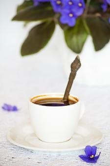 Koffiekop en schotel met paarse afrikaanse violette bloemen op een wit tafelblad.