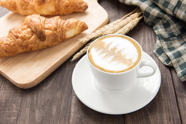 Koffiekop en verse gebakken croissants op houten achtergrond. bovenaanzicht