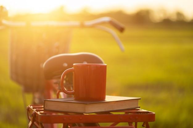Koffiekop gezet op de rode de stijl klassieke fiets van japan bij mening van groen padieveld