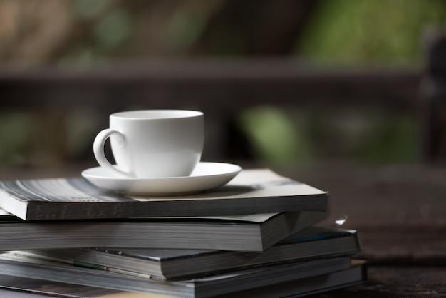 Koffiekop gezet op de stapel boeken in de ochtend.