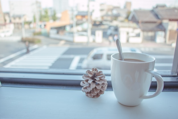 Koffiekop gezet op houten bar bij offee winkelvenster