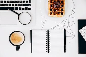 Koffiekop; laptop; vergrootglazen; spiraalvormige blocnote en wafels met chocolade op plaat tegen wit bureau