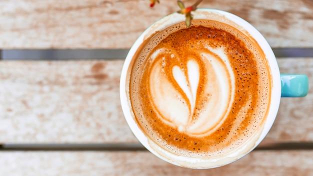 Koffiekop met de vorm van de hartvorm latte op houten lijst