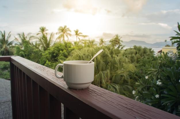 Koffiekop met koffielepel op het houten balkon