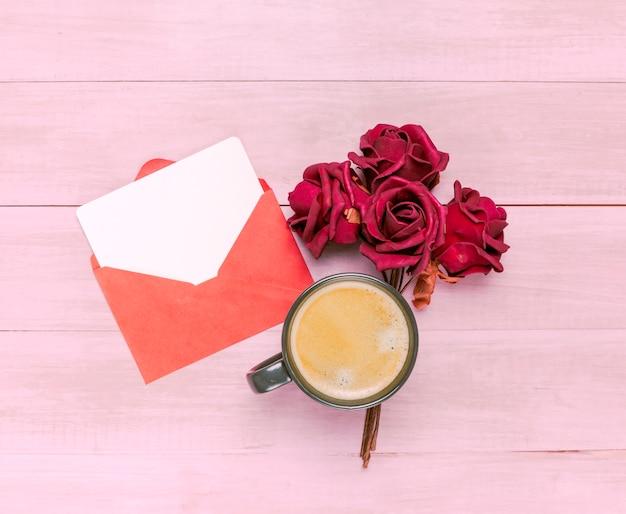 Koffiekop met rode rozen en envelop