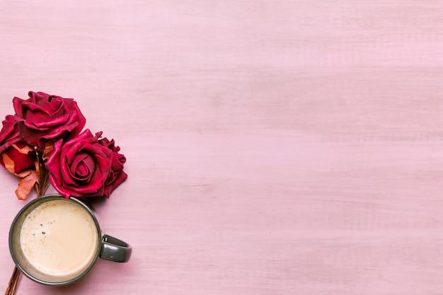 Koffiekop met rode rozen op tafel