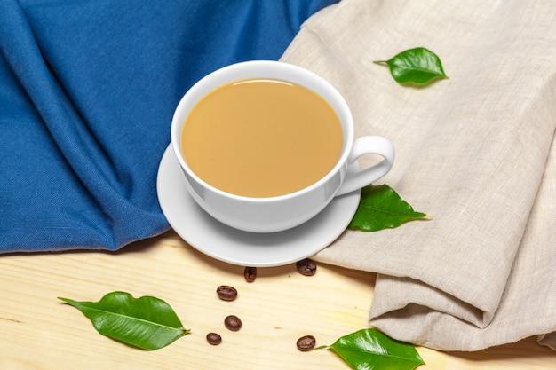 Koffiekop met schotel op een houten hoogste mening als achtergrond