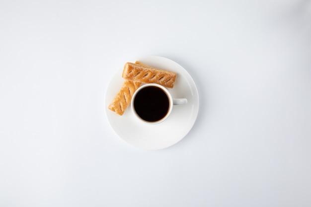 Koffiekop met snoepjes op wit worden geïsoleerd dat