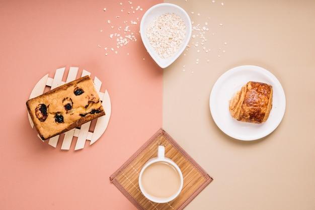 Koffiekop met taart en broodje op tafel