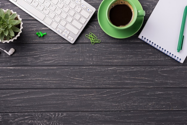 Koffiekop met toetsenbord en notitieboekje op houten bureau