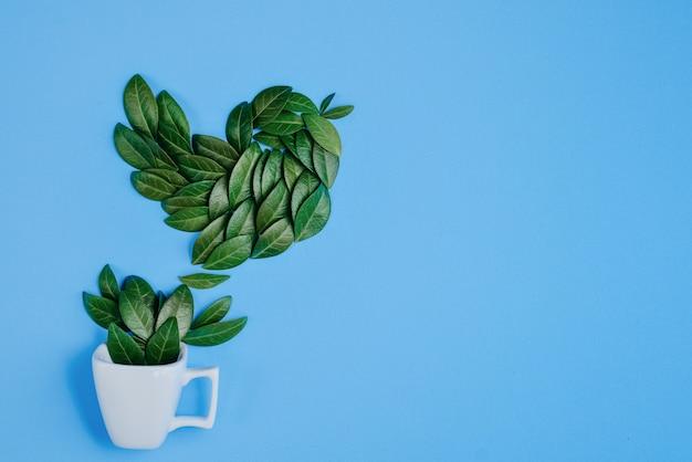 Koffiekop met vogel van natuurlijke groene bladeren op blauwe achtergrond wordt gemaakt die.